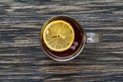Kopp te med citronen på trätabellen Royaltyfri Foto