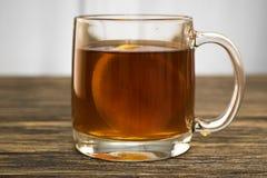Kopp te med citronen på trätabellen Royaltyfri Bild