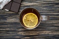 Kopp te med citronen på trätabellen Arkivfoton