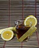 Kopp te med en citron som slås in upp av ett guld- band Royaltyfri Foto