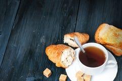 Kopp te med en giffel och ett rostat bröd på en gammal blå trätabell Arkivbild
