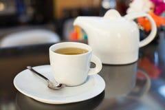 Kopp te med en tekanna i bakgrunden Fotografering för Bildbyråer