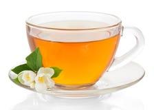 Kopp te med ett tefat och jasmin blommar royaltyfria foton