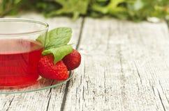 Kopp te med jordgubbar på trätabellen royaltyfri bild