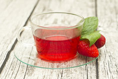 Kopp te med jordgubbar på trätabellen royaltyfri foto