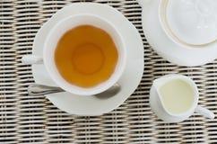 Kopp te med lite mjölkar kruset och tekannan Fotografering för Bildbyråer