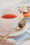 Kopp te med tesked- och kexkakor Arkivfoto