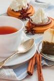Kopp te med tesked- och kexkakor Arkivbild