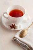 Kopp te med teskeden på kökshandduken Arkivfoto
