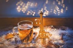 Kopp te- och Eiffeltornleksak på snö och felika ljus Arkivfoto