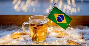 Kopp te och flagga av Brasilien på snö och felika ljus Royaltyfri Fotografi