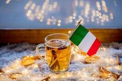 Kopp te och flagga av Italien på snö och felika ljus Arkivbilder