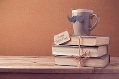Kopp te och gamla böcker för faders beröm för dag arkivbilder