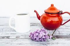 Kopp te och gammal röd tekanna på tappningträtabellen med filialen av lilan Arkivfoto