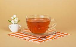 Kopp te och jasmin i liten vas royaltyfri foto