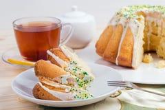 Kopp te och kaka på porslinbordsservis på broderad bordduk med påskliljan Arkivfoto