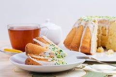 Kopp te och kaka på porslinbordsservis på broderad bordduk med påskliljan Royaltyfria Bilder
