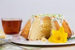 Kopp te och kaka på porslinbordsservis på broderad bordduk med påskliljan Royaltyfri Foto