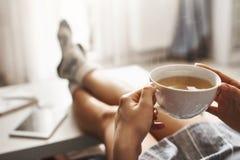 Kopp te och kyla Kvinnan som ligger på soffan och att rymma lägger benen på ryggen på kaffetabellen och att dricka varmt kaffe oc arkivfoto