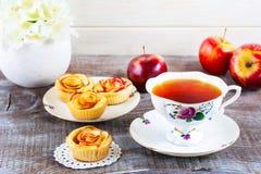 Kopp te och muffin med ros formade äppleskivor Royaltyfri Fotografi