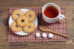 Kopp te och söta kakor arkivfoto