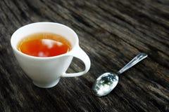 Kopp te och sked på träbakgrunds- och kopieringsutrymme arkivfoto