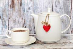 Kopp te och tekanna med hjärtaform royaltyfri bild