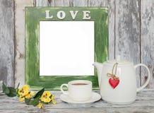 Kopp te och tekannan med hjärta formar på trätabellen arkivbild