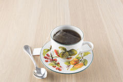 Kopp te och tesked på trätabellen arkivbild