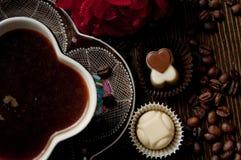 Kopp te på en wood tabell nära en ros och chokladbrända mandlar Arkivbilder