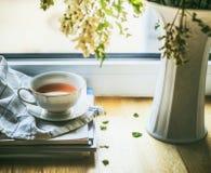 Kopp te på fönster fortfarande med vasen och blommor för livstid sommar fortfarande Royaltyfria Bilder