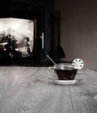 Kopp te på tabellen mot bakgrunden av brand i spisen arkivfoton