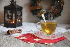 Kopp te på trätabellen med latern royaltyfri foto