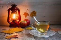 Kopp te på trätabellen med latern arkivfoton