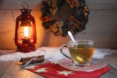Kopp te på trätabellen med rött latern royaltyfria foton