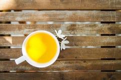 Kopp te & par av vita blommor på trätabellen Royaltyfri Bild