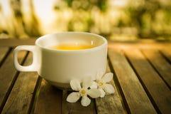 Kopp te & vita blommor på trätabellen med briljant bokeh Arkivfoto