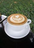Koppar av lattekonstkaffe på den svarta tabellen Arkivbilder