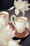 Koppar av mjölkar kaffe med blommor arkivbilder