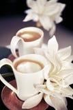 Koppar av mjölkar kaffe med blommor Royaltyfria Foton