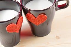 Koppar av mjölkar med dekorativa hjärtor på den wood tabellen, begrepp av valentindagen Royaltyfri Fotografi