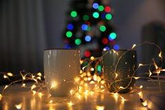 Koppar, felika ljus och suddig julgran i rum royaltyfria bilder
