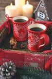 Koppar kaffe och kanelbruna pinnar, brännande stearinljus och sörjer Co Arkivfoton
