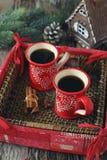 Koppar kaffe och kanelbruna pinnar, brännande stearinljus och sörjer Co Arkivbilder