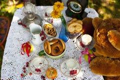 Koppar med milc, bunkar med kakor och nya bär - hallonet, körsbär - på bordduk Arkivfoto