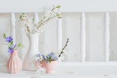 koppar och vaser med blommor på tappningträvit hylla royaltyfria bilder