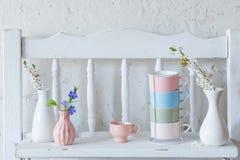 koppar och vaser med vårblommor på trävit hylla royaltyfri bild