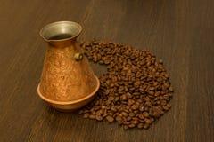 Kopparcezve för kaffe med kaffebönor Arkivfoto