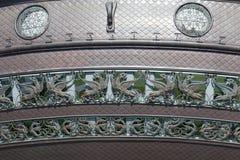 Koppardiagram av drakar och bevingade lejon på byggnaden Arkivfoto