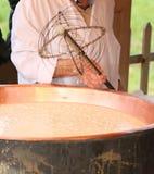 Kopparkrukan med mjölkar för framställning av ost i bergmejerit Arkivfoton